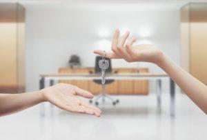 Mani con chiavi sfondo ufficio interno